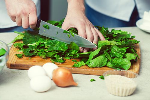 Healthy eating in kitchen cutting elderly knife